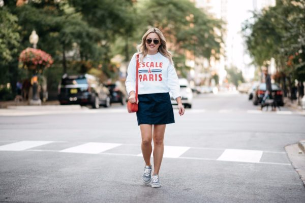 Bows & Sequins wearing a Paris-inspired sweatshirt with an Old Navy suede skirt and Claudie Pierlot navy gingham sneakers.