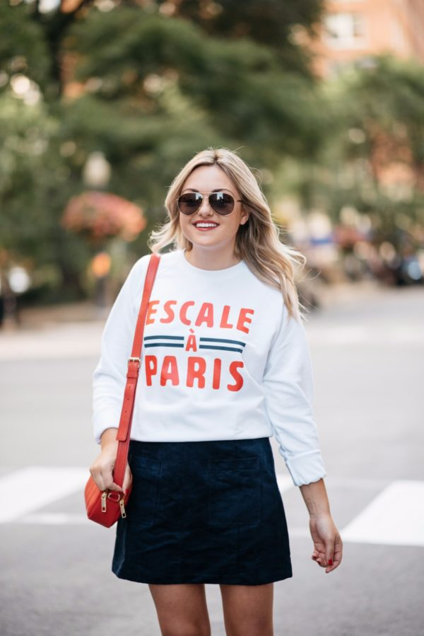 Bows & Sequins wearing Gucci aviators, a French Disorder Paris sweatshirt, and an Old Navy blue suede skirt with a Talbots red leather bag.