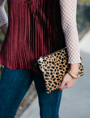 Bows & Sequins wearing a sheer lace turtleneck, a velvet cami, and skinny jeans with a Clare V leopard clutch and a gold cuff.