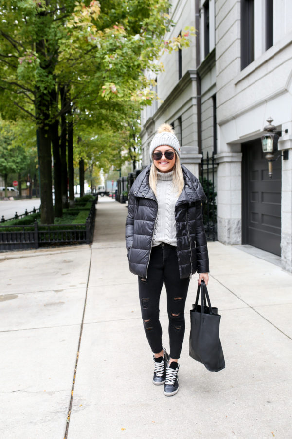 Jessica Sturdy wearing a Barbour quilted jacket with a cable knit sweater, Ashridge beanie, Old Navy black denim, and Kim & Zozi glitter sneakers with a black leather tote.