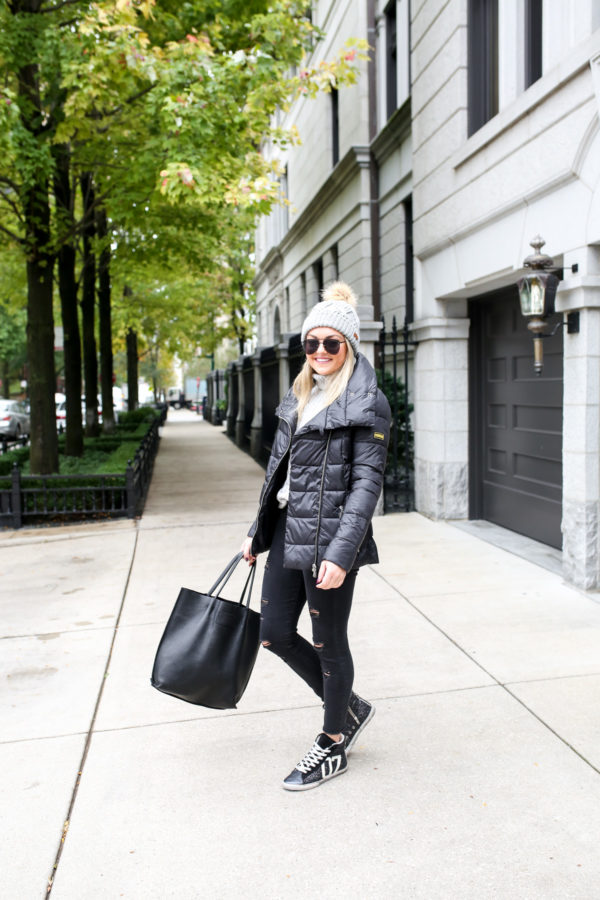 Jessica Sturdy wearing a Barbour Ashridge beanie, a quilted Rockingham down jacket, Old Navy black denim, and glitter sneakers with a black leather tote.