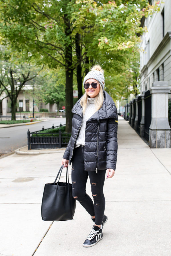 Chicago blogger Jessica Sturdy wearing a Barbour quilted jacket with a cable knit sweater, Ashridge beanie, Old Navy black denim, and Kim & Zozi glitter sneakers with a black leather tote.