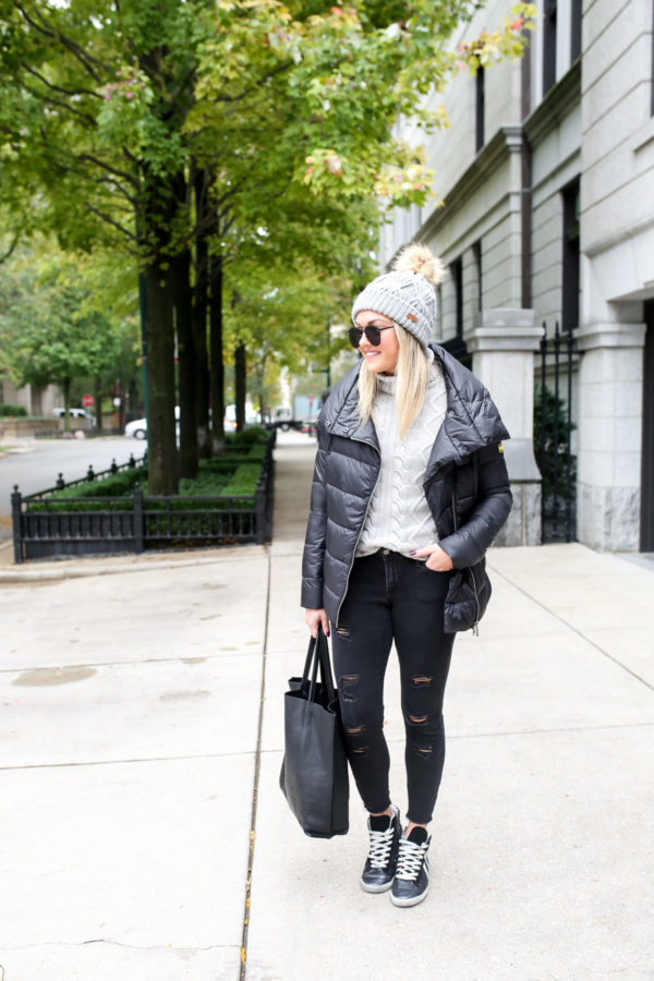 Chicago lifestyle blogger Bows & Sequins wearing a Barbour fur pom beanie, aviators, a Barbour Rockingham jacket, grey turtleneck sweater, Old Navy black denim, and glitter sneakers with a black leather tote.