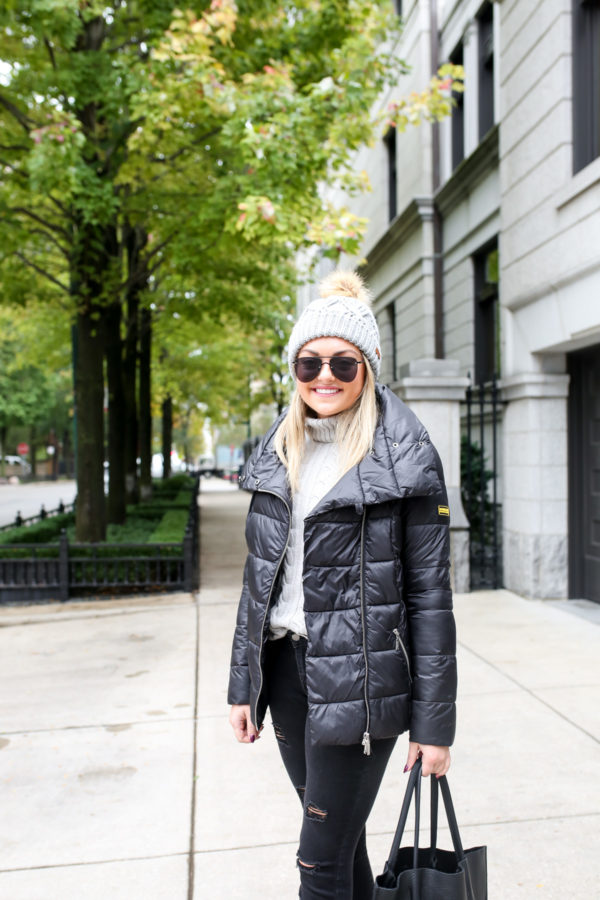 Jessica Rose Sturdy of Bows & Sequins wearing a Barbour black quilted jacket with an Ashridge beanie and a grey turtleneck sweater with Old Navy black jeans and a leather tote.