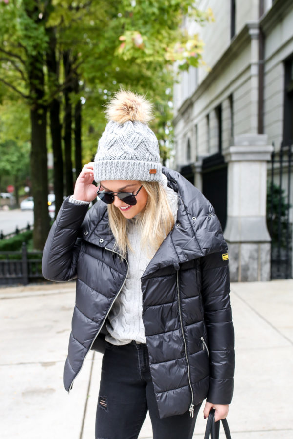 Jessica Sturdy, of the fashion and lifestyle blog Bows & Sequins, wearing a Barbour fur pom grey beanie, a Rockingham quilted jacket, and turtleneck sweater.