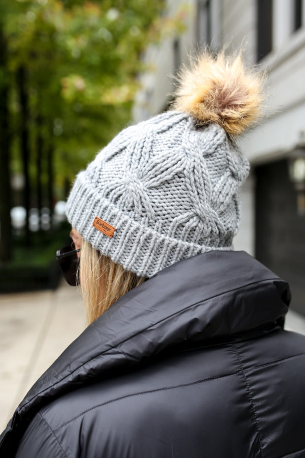 Jessica Sturdy of Bows & Sequins wearing a fur pom beanie and Barbour Rockingham jacket.