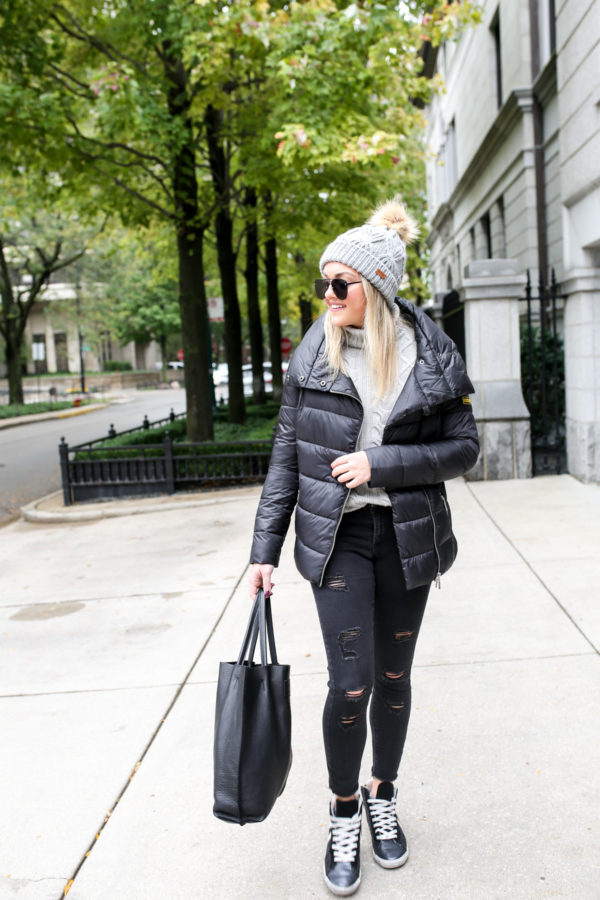Fashion and lifestyle blogger Jessica Sturdy wearing a Barbour quilted jacket with a cable knit sweater, Ashridge beanie, Old Navy black denim, and Kim & Zozi glitter sneakers with a black leather tote.