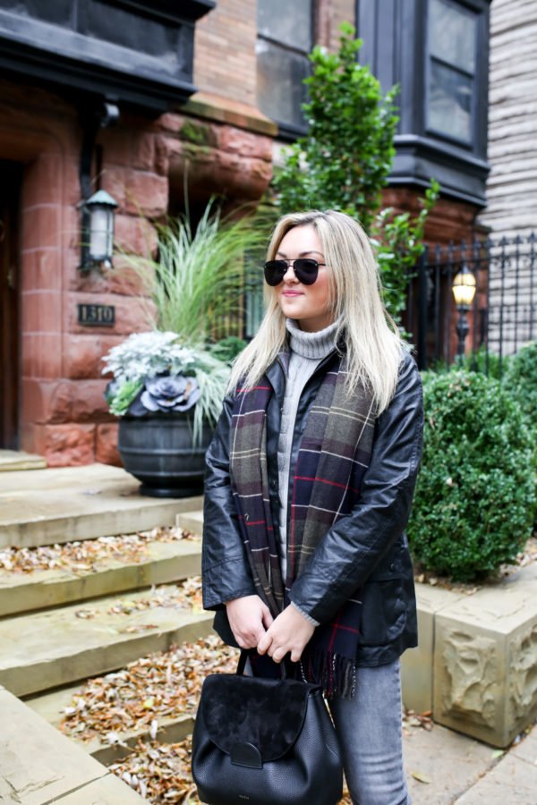 Jessica Sturdy wearing Le Specs matte black aviators, a Barbour Beadnell jacket, grey turtleneck sweater, and a tartan scarf with a Polene bag.