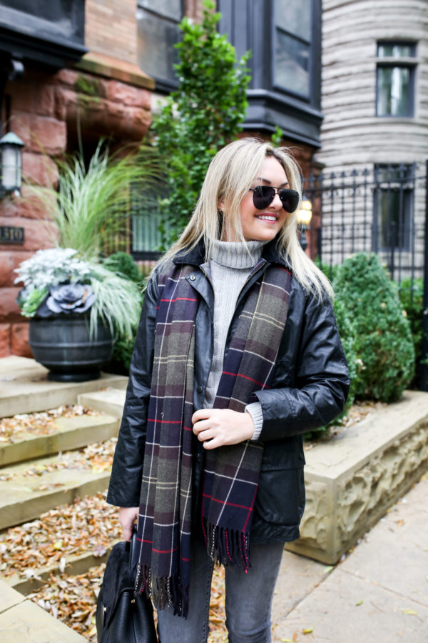 Jessica Sturdy wearing matte black aviators and a Barbour Beadnell jacket with a grey turtleneck and tartan scarf.