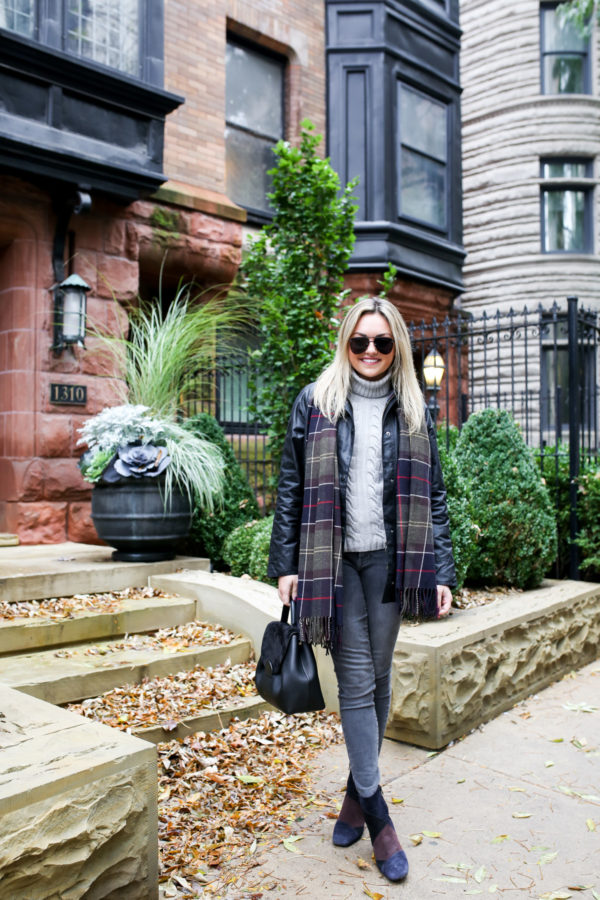 Jessica Sturdy of Bows & Sequins wearing a Barbour black Beadnell jacket with grey jeans and patchwork booties in Chicago.