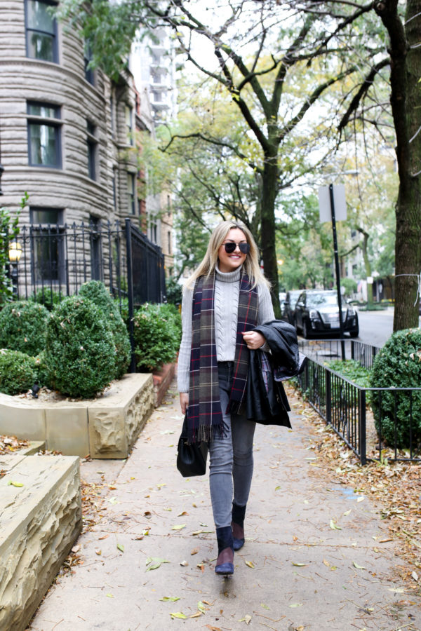 Jessica Sturdy of Bows & Sequins wearing a Barbour black Beadnell jacket with a cable knit grey sweater, grey jeans, and patchwork booties with a tartan scarf in Chicago.