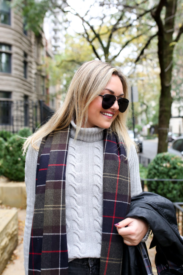 Jessica Sturdy wearing Le Specs aviators, a Barbour grey turtleneck cable knit sweater and a tartan scarf.