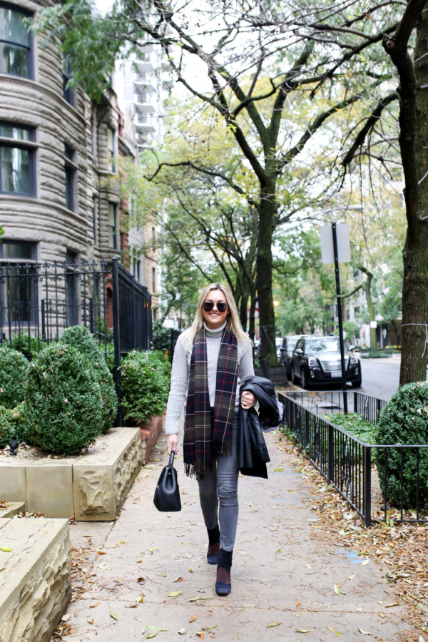 Jessica Sturdy of Bows & Sequins wearing a Barbour black Beadnell jacket with a cable knit grey sweater, Old Navy grey jeans, and Andre Assous patchwork booties with a tartan scarf in Chicago.