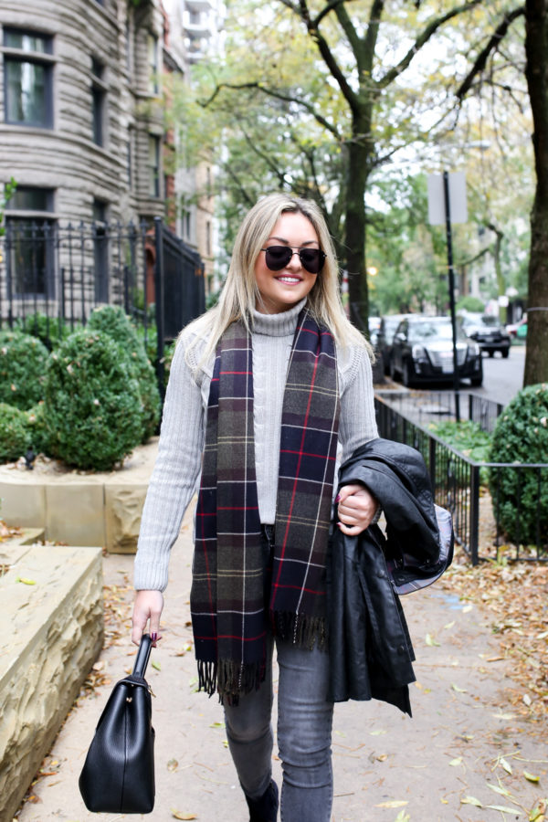 Jessica Sturdy of Bows & Sequins wearing a Barbour black Beadnell jacket with a cable knit grey sweater, Old Navy grey jeans, and Andre Assous patchwork booties with a tartan scarf and a Polene bag in Chicago.