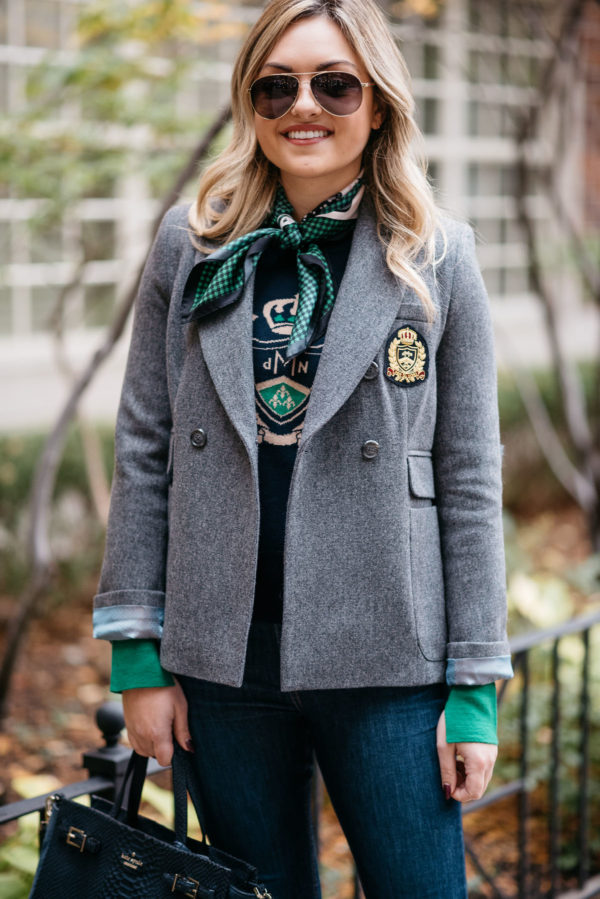 Jessica Rose Sturdy of Bows & Sequins wearing a grey MDN blazer, navy crest sweatshirt, a silk neck scarf and Rag & Bone skinny jeans with Gucci aviators and a navy Kate Spade tote.