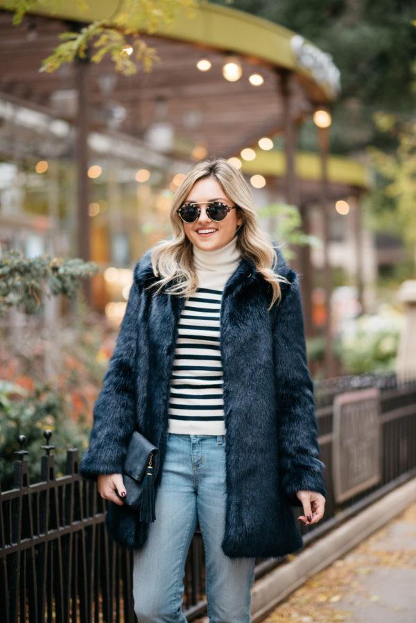Fashion blogger Bows & Sequins wearing Illesteva sunglasses, Miranda Dunn London faux fur coat, MDN striped turtleneck and Vineyard Vines boyfriend jeans.