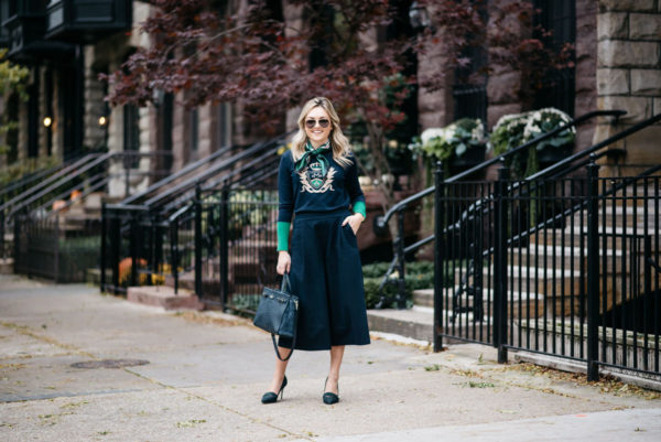 Jessica Sturdy wearing Gucci aviators, a silk neck scarf, MDN green and navy crest sweater, Old Navy blue culotte pants, and J.Crew blackwatch plaid pumps with a Kate Spade navy tote.
