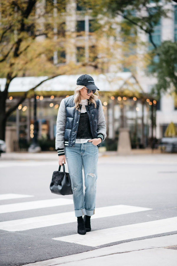Jessica Sturdy wearing a baseball cap, a Veronica Beard puffer bomber jacket, an Endless Rose layered tee and crochet tank, Levi 501 Jeans, Steve Madden lucite booties, and a Polene Paris top-handle bag.