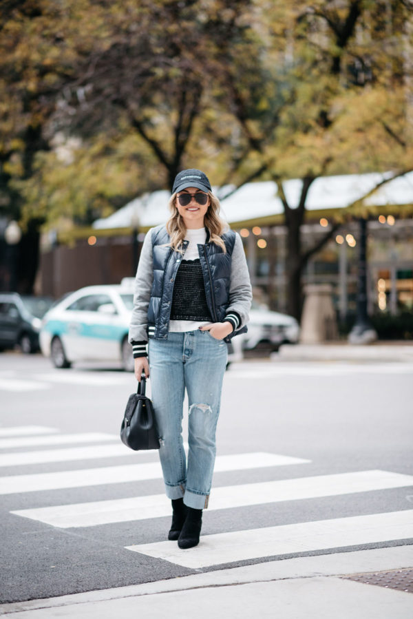 Jessica Sturdy wearing a baseball cap, Le Specs matte black aviators, a Veronica Beard puffer bomber jacket, an Endless Rose layered tee and crochet tank, Levi 501 Jeans, Steve Madden lucite booties, and a Polene Paris top-handle bag.