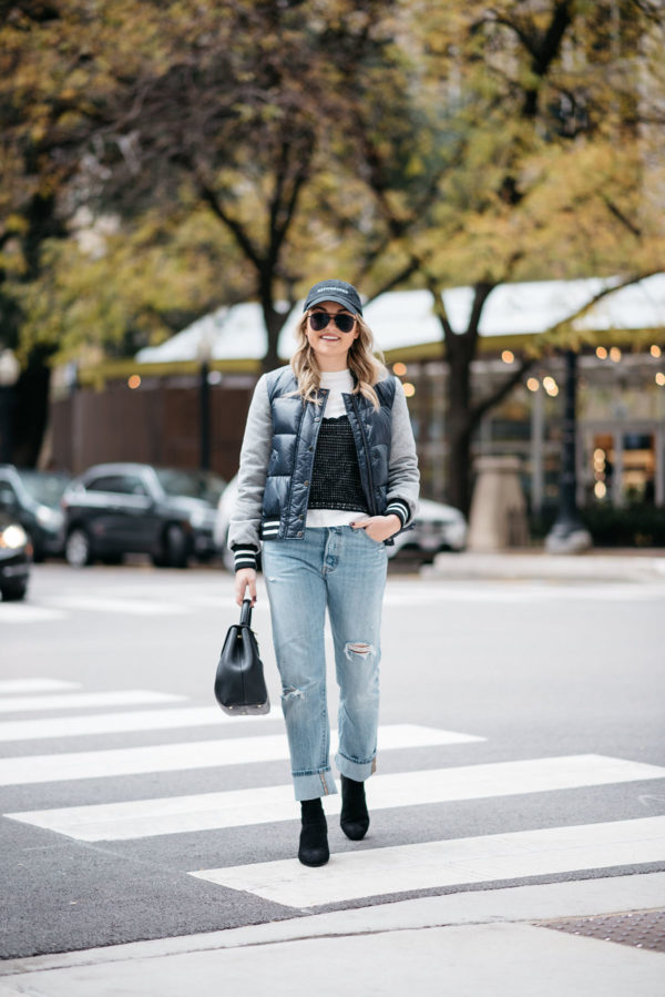 Chicago fashion and lifestyle blogger Jessica Sturdy wearing a baseball cap, Le Specs matte black aviators, a Veronica Beard puffer bomber jacket, an Endless Rose layered tee and crochet tank, Levi 501 Jeans, Steve Madden lucite booties, and a Polene Paris top-handle bag.
