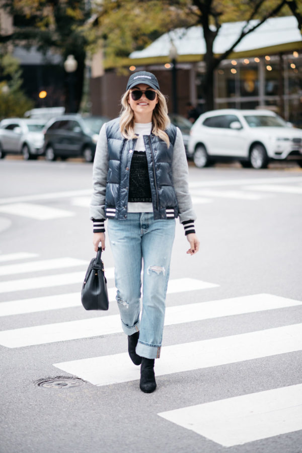 Fashion-focused blogger Jessica Rose Sturdy wearing a baseball cap, a Veronica Beard puffer bomber jacket, an Endless Rose layered tee and crochet tank, Levi 501 Jeans, Steve Madden lucite booties, and a Polene Paris top-handle bag.
