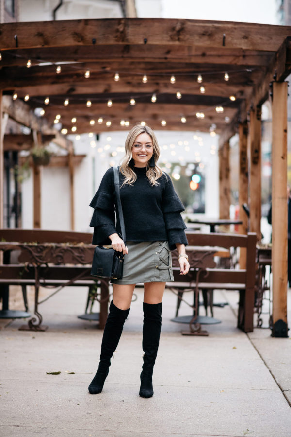 Jessica Sturdy wearing a black ruffle sleeve sweater, olive green lace-up mini skirt, black suede over the knee boots, a Lancel crossbody bag, and clear aviator glasses.