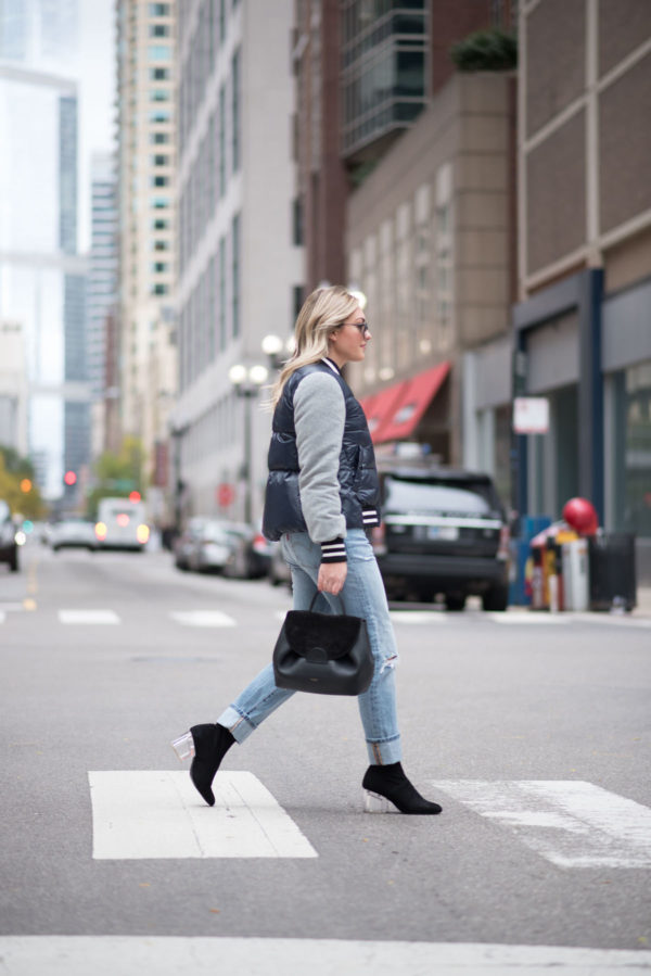 Chicago blogger Jessica Sturdy wearing a baseball cap, a Veronica Beard puffer bomber jacket, an Endless Rose layered tee and crochet tank, Levi 501 Jeans, Steve Madden lucite booties, and a Polene Paris top-handle bag.