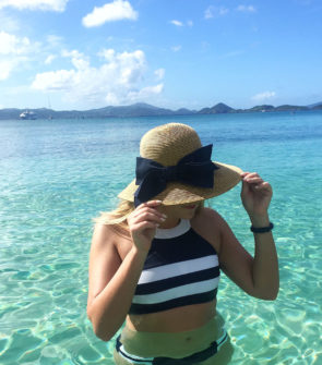 Jessica Sturdy in the USVI at Caneel Bay wearing a straw hat with a bow and a navy and white striped bikini swimsuit.