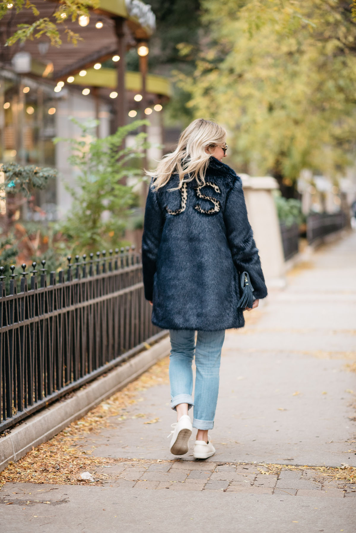 Fashion blogger Jessica Rose Sturdy wearing a leopard-print monogrammed faux fur Miranda Dunn coat with Vineyard Vines boyfriend jeans and Sezane Paris Jack leather sneakers.