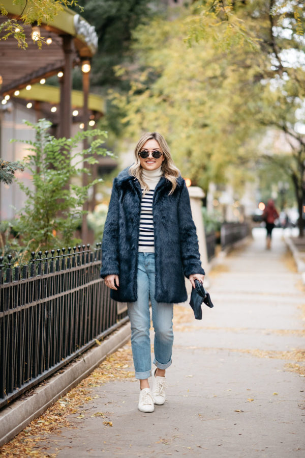 Fashion and lifestyle blogger Jessica Sturdy of Bows & Sequins wearing Illesteva sunglasses, an MDN striped turtleneck, Miranda Dunn London faux fur coat, Vineyard Vines boyfriend jeans, and Sezane Jack leather sneakers with an Azalea Jack foldover clutch.