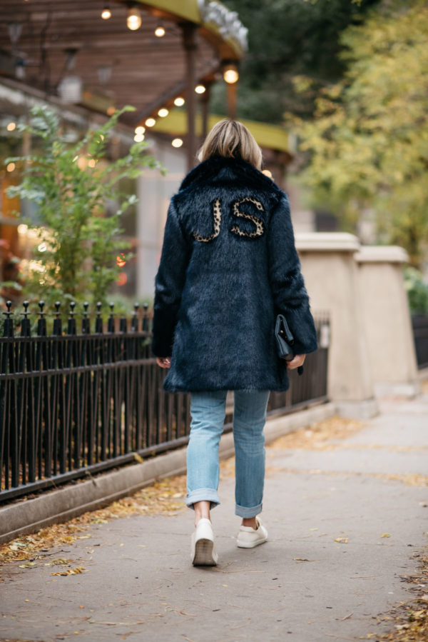 Fashion blogger Jessica Rose Sturdy wearing a leopard-print monogrammed faux fur Miranda Dunn coat with Vineyard Vines boyfriend jeans and Sezane Paris Jack leather sneakers.