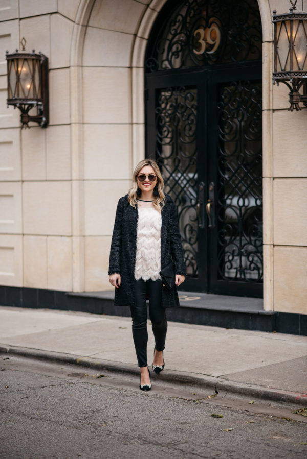 Chicago fashion blogger Jessica Rose Sturdy wearing Gucci aviators, a Sail to Sable holiday tweed coat, a fringe tunic, Express black waxed jeans, and Kate Spade bow pumps with Hart tassel earrings and an Old Navy clutch.