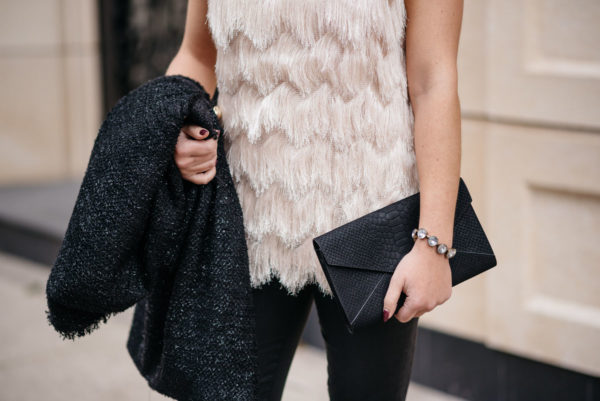 Jessica Sturdy of Bows & Sequins wearing a Sail to Sable fringe top with a J.Crew rhinestone bauble bracelet, a sparkly tweed coat, and an Old Navy clutch for the holidays.