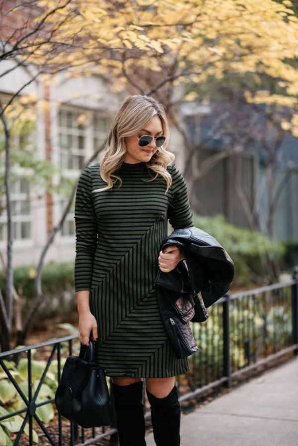 Jessica Sturdy of Bows & Sequins wearing gold Ray-Ban aviators, a green striped Hutch dress from Anthropologie, suede over the knee boots, and a Topshop moto jacket with a Polene top-handle bag.