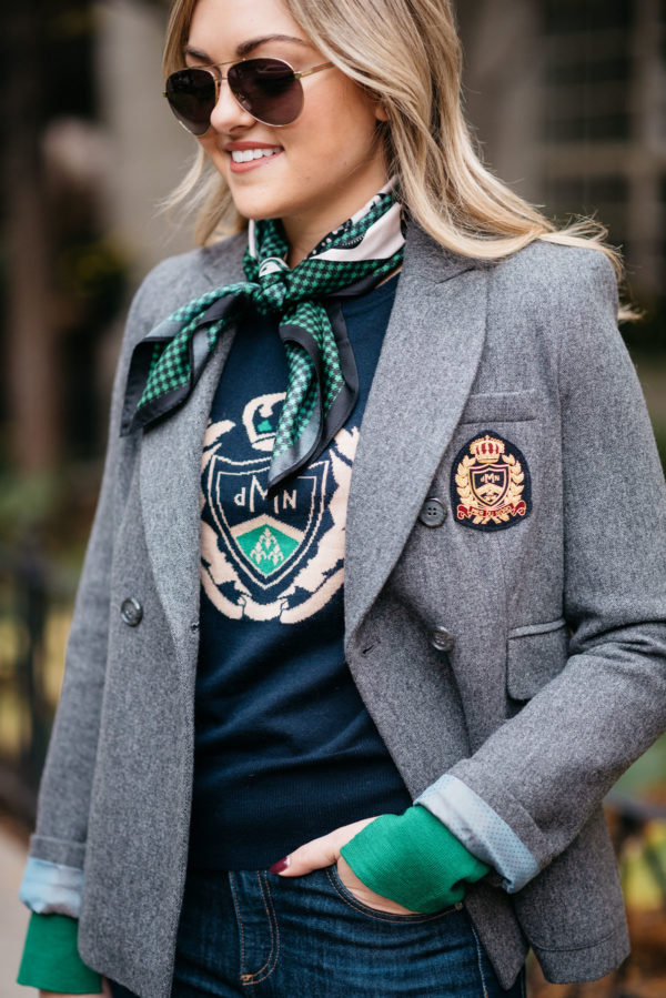 Jessica Sturdy wearing a MDN silk neck scarf, a navy crest sweatshirt, and a grey blazer.
