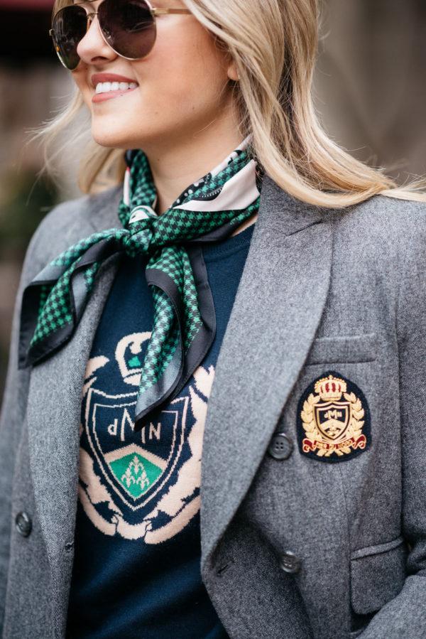 Jessica Sturdy wearing a green print silk neck scarf, navy crest sweatshirt, and a grey MDN blazer.