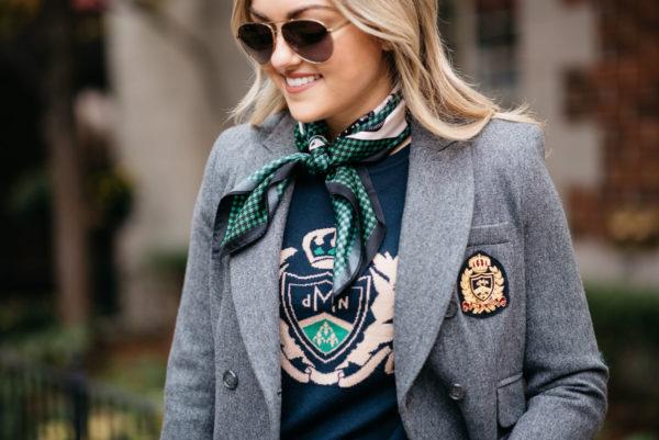 Jessica Sturdy wearing a green print silk neck scarf, navy crest sweatshirt, and a grey MDN blazer with Gucci aviators.