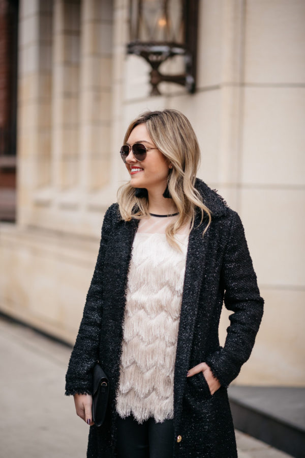 Jessica Sturdy wearing Gucci aviators, a Sail to Sable tweed coat, fringe holiday top, and Hart tassel earrings.