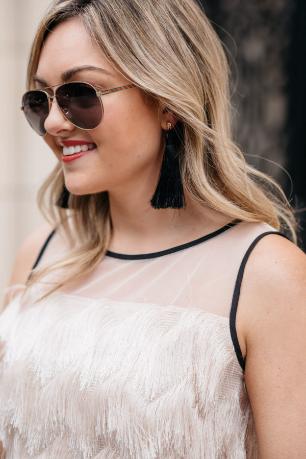 Jessica Rose Sturdy wearing Gucci aviators, Hart tassel earrings, and a Sail to Sable fringe top.