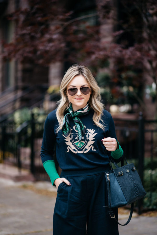 Chicago fashion-focused blogger Jessica Sturdy wearing Gucci aviators, a silk neck scarf and a MDN crest sweater with a Kate Spade tote bag.