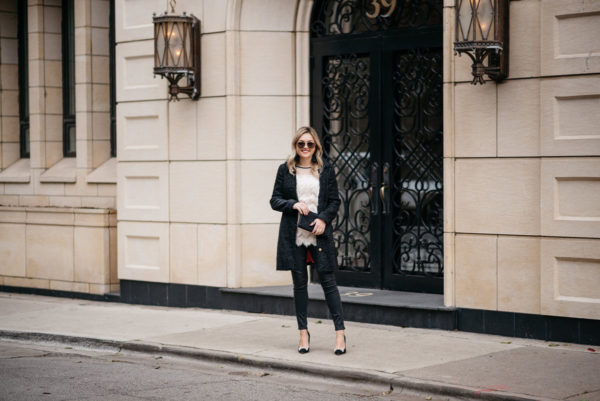 Lifestyle and fashion blogger Jessica Rose Sturdy wearing Gucci aviators, a Sail to Sable holiday tweed coat, a fringe tunic, Express black waxed jeans, and Kate Spade bow pumps with Hart tassel earrings and an Old Navy clutch.