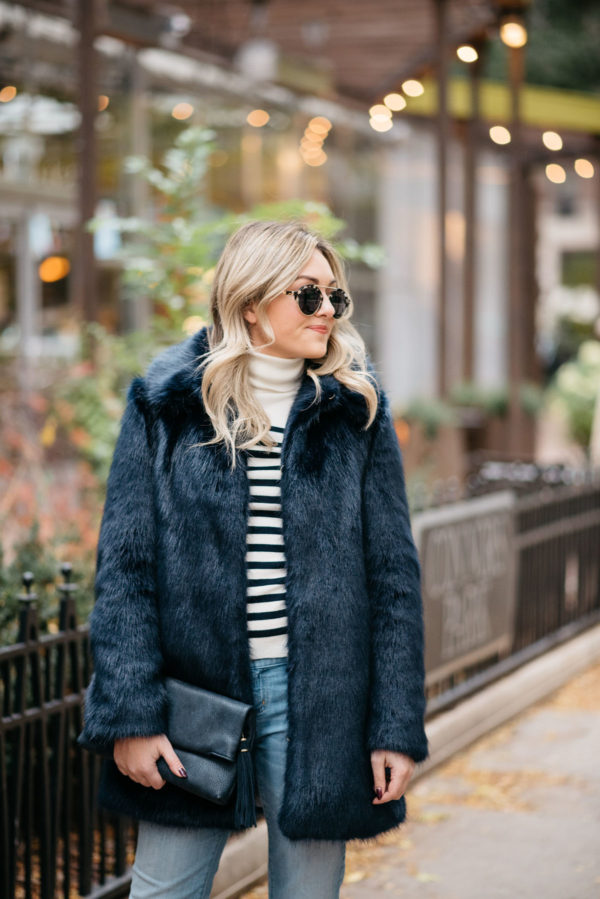 Fashion and lifestyle blogger Jessica Sturdy of Bows & Sequins wearing Illesteva sunglasses, an MDN striped turtleneck, Miranda Dunn London faux fur coat and an Azalea Jack foldover clutch.