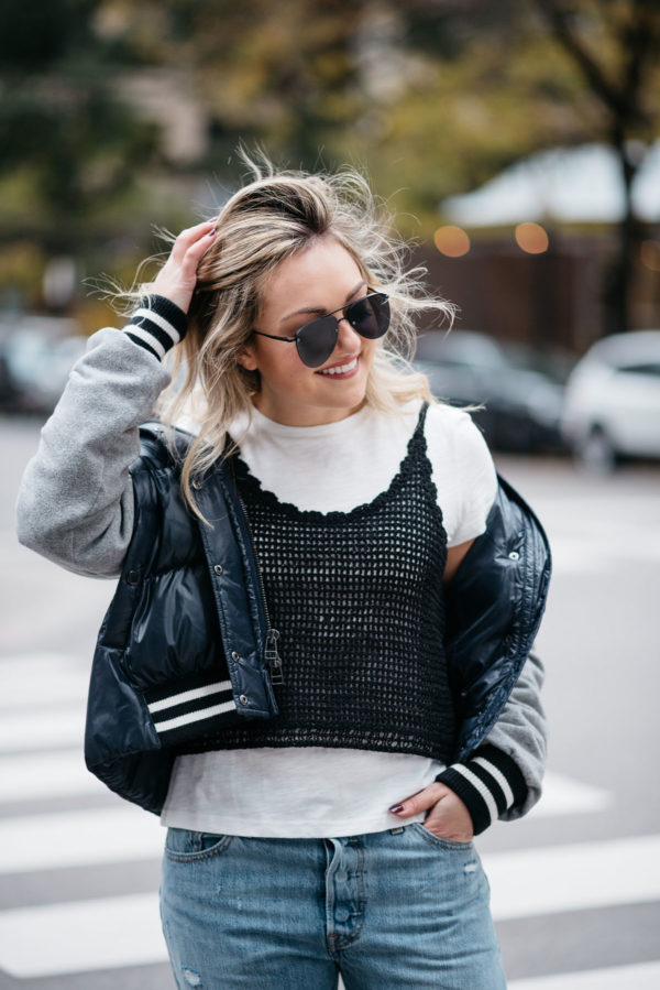 Jessica Sturdy wearing Le Specs matte black aviators, a Veronica Beard puffer bomber jacket, and an Endless Rose layered tee and crochet tank.