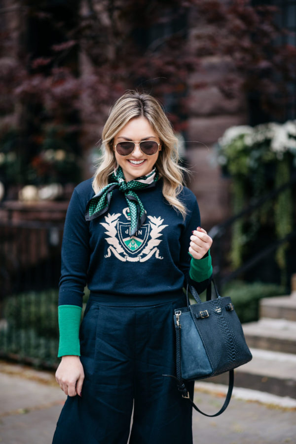 Jessica Rose Sturdy wearing Gucci aviators, a silk neck scarf and a MDN crest sweater with a Kate Spade tote bag.