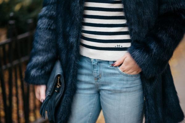 Jessica Sturdy wearing a Miranda Dunn London faux fur coat, MDN striped turtleneck and Vineyard Vines boyfriend jeans with an Azalea Blue foldover clutch.