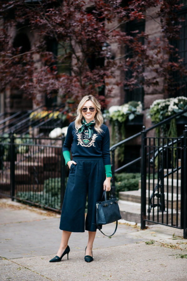 Jessica Rose Sturdy wearing Gucci aviators, a silk neck scarf, MDN green and navy crest sweater, Old Navy blue culotte pants, and J.Crew blackwatch plaid pumps with a Kate Spade navy tote.