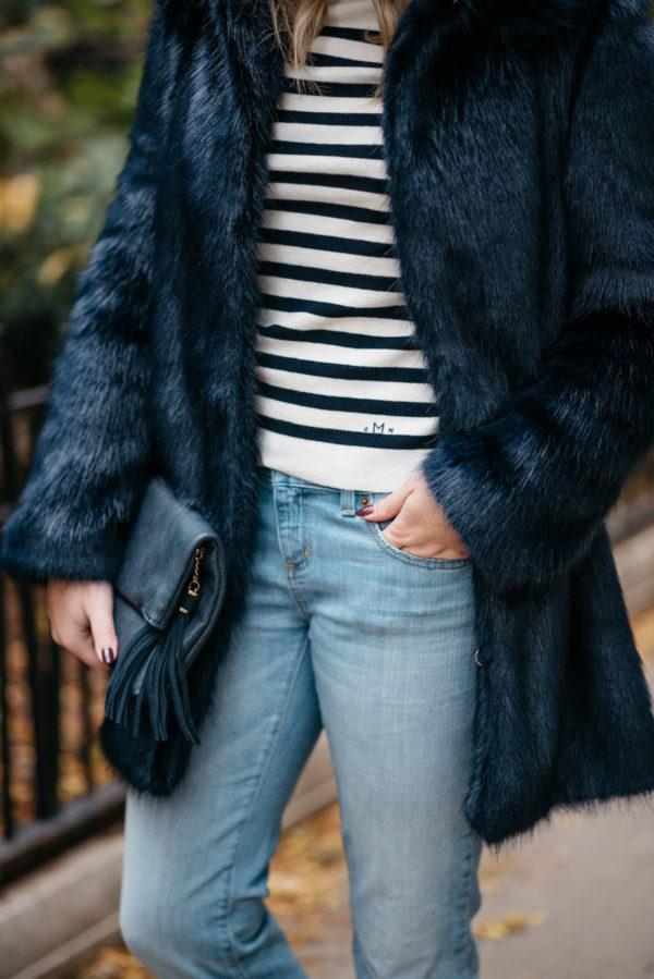 Fashion blogger Bows & Sequins wearing a Miranda Dunn London faux fur coat, MDN striped turtleneck and Vineyard Vines boyfriend jeans with an Azalea Blue foldover clutch.