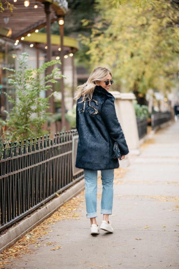 Fashion blogger Jessica Rose Sturdy wearing a leopard-print monogrammed faux fur Miranda Dunn coat with Illesteva sunglasses, Vineyard Vines boyfriend jeans, and Sezane Paris Jack leather sneakers.