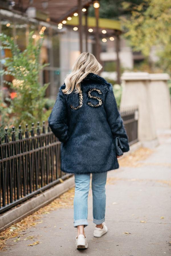 Fashion and lifestyle blogger Jessica Rose Sturdy wearing a leopard-print monogrammed faux fur Miranda Dunn coat with Illesteva sunglasses, Vineyard Vines boyfriend jeans, and Sezane Paris Jack leather sneakers.