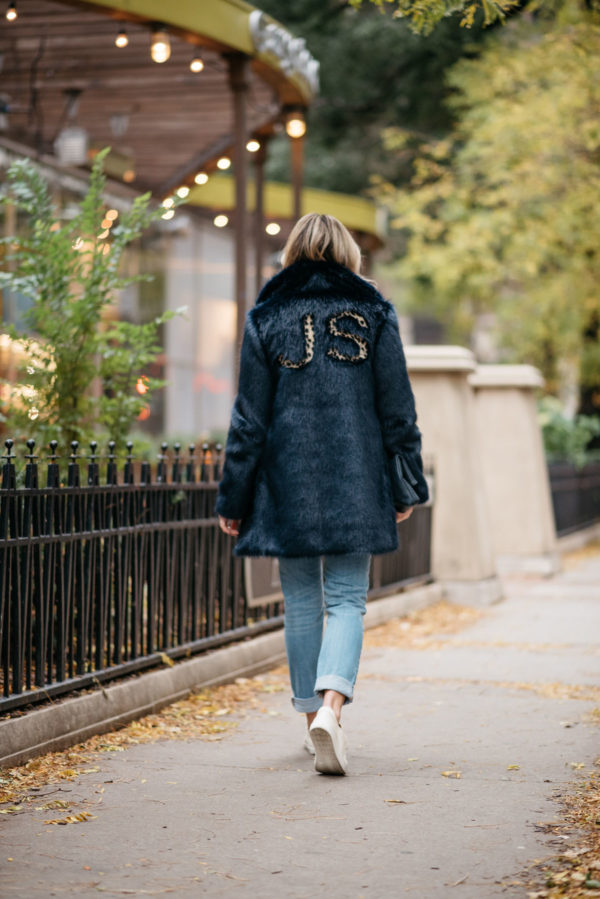 Jessica Rose Sturdy wearing a leopard-print monogrammed faux fur Miranda Dunn coat with Vineyard Vines boyfriend jeans and Sezane Paris Jack leather sneakers.